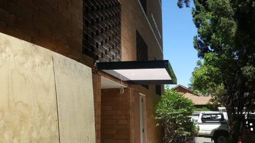 Slimline awning over a door way in to a block of units